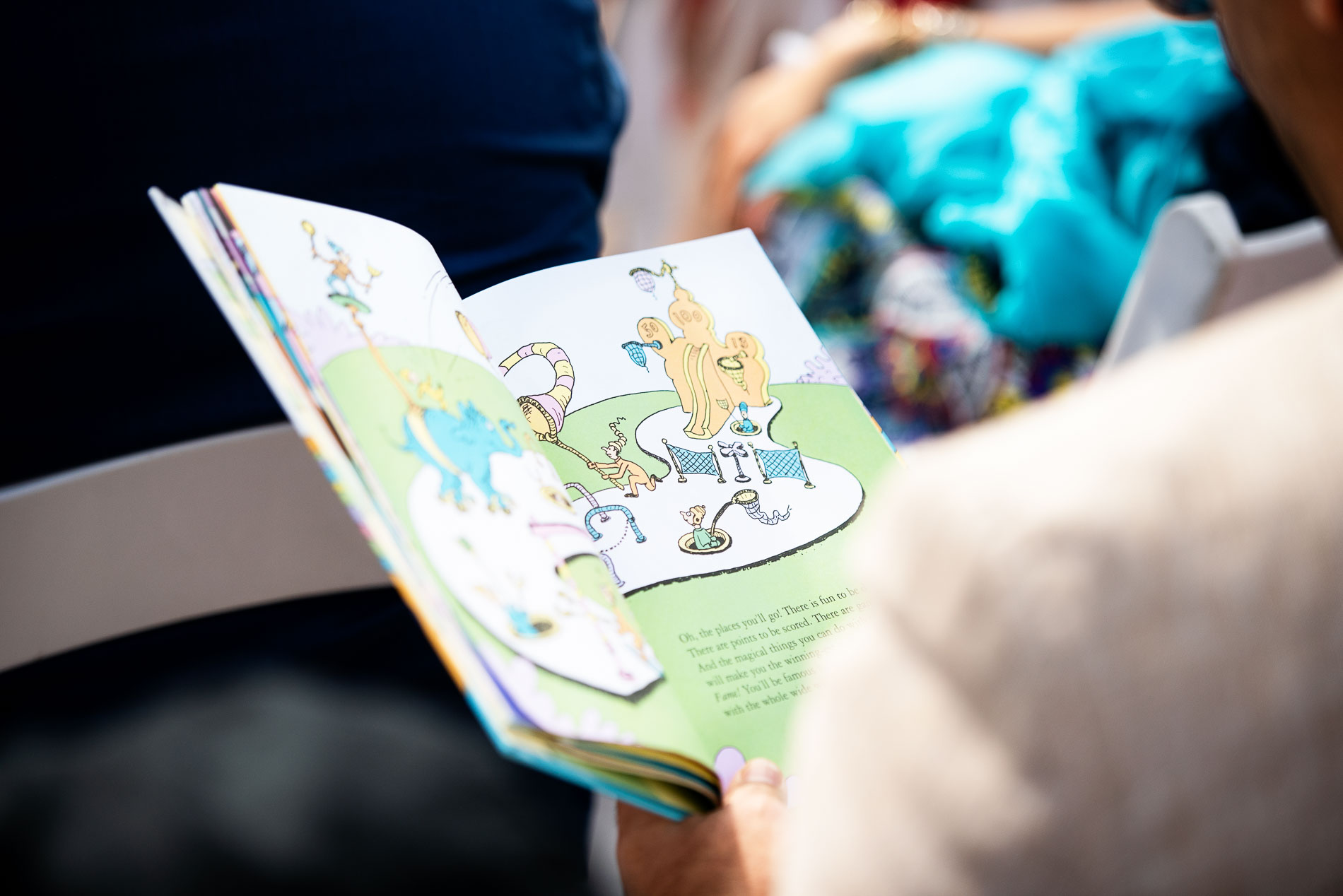 A Close Up Shot Of Page From Dr Seuss Oh The Places You Ll Go As Guests Read It During Holmes Beach Wedding Ceremony
